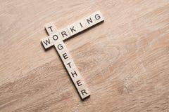 Arbeta tillsammans ord samlade av modiga kuber på träyttersida royaltyfria foton