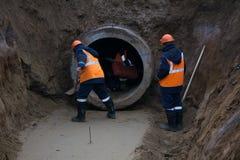 Arbeta under jordningen med ett stort konkret rör våt lera Arbetare i overaller, hjälm, skyddande kängor En djup utgrävning royaltyfria bilder
