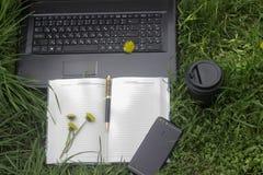 Arbeta utomhus med telefonen, bärbara datorn och coffe arkivbilder