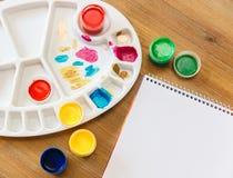 Arbeta utrymme med den öppna anmärkningsboken, målarfärger table trä Royaltyfria Foton