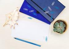 Arbeta utrymme med det tomma arket, ben, blyertspennor, exponeringsglas, anmärkningsbok Skapa Arkivbilder