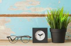Arbeta utrymme som är dekorativt med krukaove för exponeringsglas, för klockan och för grönt gräs Arkivfoto