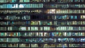 Arbetande afton i exponeringsglaskontorsbyggnad med talrika kontor med glasv?gg- och f?nstertimelapse