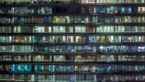 Arbetande afton i exponeringsglaskontorsbyggnad med talrika kontor med glasv?gg- och f?nstertimelapse lager videofilmer