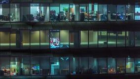 Arbetande afton i exponeringsglaskontorsbyggnad med talrika kontor med glasv?gg- och f?nstertimelapse arkivfilmer