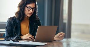 Arbetande bärbar dator för asiatisk kvinna på kontoret royaltyfri bild