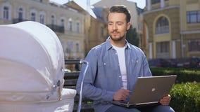 Arbetande bärbar dator för man och le till spädbarnet i vagnen, multitasking som är frilans- lager videofilmer