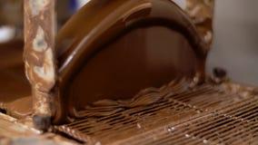 Arbetande chokladbeläggningsmaskin på konfekt arkivfilmer