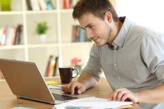 Arbetande kontrollera för Freelancer på linjen innehåll hemma arkivfoton