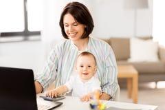 Arbetande mamman med behandla som ett barn pojken och b?rbara datorn hemma arkivfoton