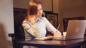 Arbetande sen cocncept Kvinnan som tänker om anmärkningarna i den rekord- boken Stående glidare 4K arkivfilmer