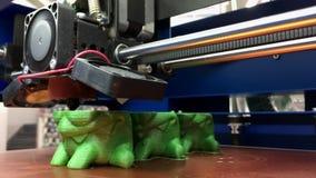 Arbetande skrivare som 3D skrivar ut leksaker från grön plast- med tillsatsteknologi stock video