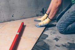 Arbetande tegelplattor lägger på golvet royaltyfria foton