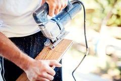 Arbetar den bitande wood parketten för arbetaren som använder cirkelsågen under hemförbättring Arkivbild