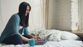 Arbetar den lyckliga freelanceren för den härliga kvinnan hemma genom att använda bärbara datorn och le se den frilans- skärmen o arkivfilmer