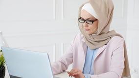 Arbetar den muslim kvinnan f?r nerden i hijab p? ett avl?ggande av examenungkarlprojekt som skriver p? b?rbara datorn och ser sma arkivfilmer