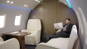 Arbetar den respektabla mannen för den unga analytikeren för aktieägaren sakkunniga på projektsammanträde i privat flygplan stock video
