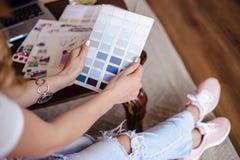 Arbetar den unga kvinnan för dekoratören med färgpaletten, tillfälligt foto för livsstil royaltyfri foto
