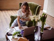 Arbetar den unga kvinnan för dekoratören med färgpaletten, tillfälligt foto för livsstil royaltyfri bild
