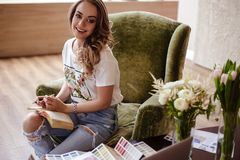 Arbetar den unga kvinnan för dekoratören med färgpaletten, tillfälligt foto för livsstil arkivbilder