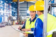 Arbetar- och gaffeltruckchaufför i industriell fabrik Fotografering för Bildbyråer