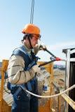 Arbetarbyggmästare på fasadinstallationsarbete med att nita hammaren royaltyfria foton