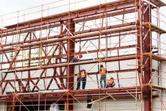 Arbetarbyggmästare som arbetar på takstrukturen på konstruktionsplats Byggnadslag royaltyfri foto