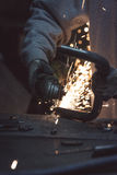 Arbetarcuttingmetall med grinderen Gristrar flyg, medan mala Royaltyfri Fotografi