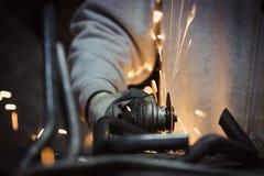 Arbetarcuttingmetall med grinderen Gristrar flyg, medan mala Fotografering för Bildbyråer