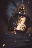 Arbetarcuttingmetall med grinderen Gristrar flyg, medan mala Royaltyfri Foto