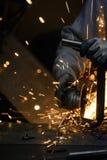 Arbetarcuttingmetall med grinderen Gristrar flyg, medan mala stålröret Royaltyfri Fotografi