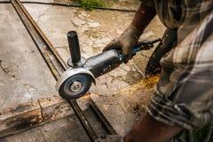 Arbetarcuttingmetall med grinderen malande järnsparks Royaltyfri Foto