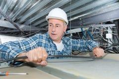Arbetardanandebeslag för elektrisk kabel i tak fotografering för bildbyråer
