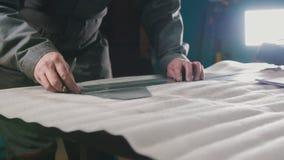Arbetardanandemätningar och fläckar på en del med hjälp av en linjal arkivbild