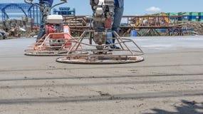 Arbetare använder betongpoleringsmaskiner för cement, når de har hällt klar-blandad betong arkivfoto