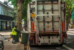 Arbetare av stads- kommunal avfalls f?r p?fyllning f?r lastbil f?r ?tervinningavskr?desamlare och avfallfacket royaltyfri bild