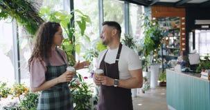 Arbetare av talande le för blommalager rymma kaffe under avbrott i arbetsplats lager videofilmer