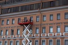 Arbetare behandlade fasaden av huset på en hög elevator Royaltyfria Bilder