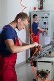 Arbetare bredvid maskiner i fabrik Royaltyfria Bilder
