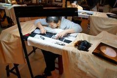 Arbetare broderar med silke Royaltyfria Bilder