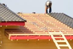 Arbetare bygger ett tak på huset royaltyfria bilder