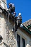 Arbetare för Abseiling byggnadsunderhåll på arbete Arkivfoton
