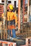 arbetare för arbete för byggmästarebetong hällande Arkivfoton