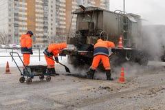 Arbetare för asfaltväg i en liten grop på huvudvägen Arkivbilder