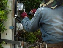 Arbetare för elektrikerlinjearbetarerepairman på klättringarbete på electri Royaltyfria Foton