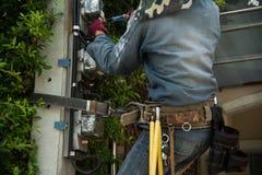 Arbetare för elektrikerlinjearbetarerepairman på klättringarbete på electri Royaltyfria Bilder