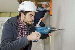 Arbetare för konstruktionsplats som borrar med maskinen eller drillborren royaltyfri bild