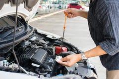 Arbetare för för man som eller automatisk mekaniker kontrollerar det bilmotoroljan och underhållet, innan att resa för säkerhet royaltyfria bilder