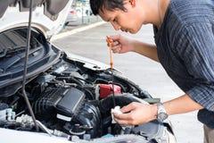 Arbetare för för man som eller automatisk mekaniker kontrollerar det bilmotoroljan och underhållet, innan att resa för säkerhet fotografering för bildbyråer