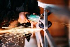 Arbetare för tung bransch som klipper stål med vinkelmolar på konstruktionsplats arkivbilder